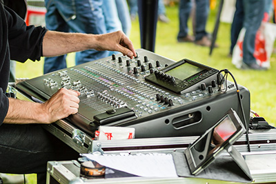 Hands using audio mixing board on outdoors concert.